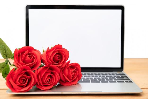Maquete de rosa e laptop vermelho em branco