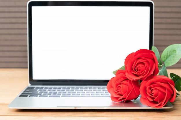Maquete de rosa e laptop vermelho na madeira