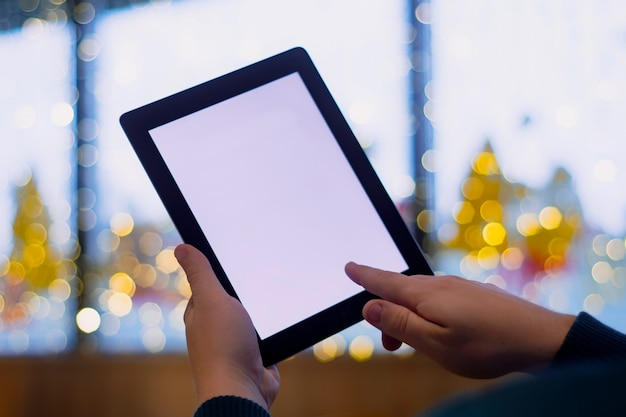 Maquete de tablet de close-up com tela branca. um freelancer masculino trabalha em um café.