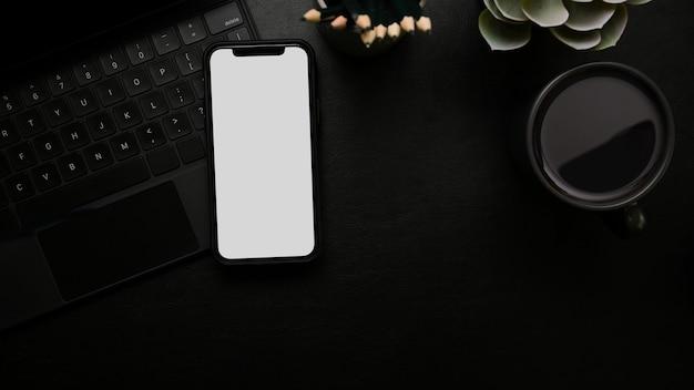 Maquete de tela branca do smartphone moderno na área de trabalho na vista superior da superfície preta do teclado de magia negra