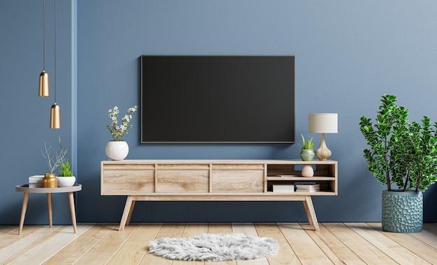 Maquete de televisão no gabinete em uma sala vazia contemporânea com uma parede azul escura atrás dela. renderização em 3d