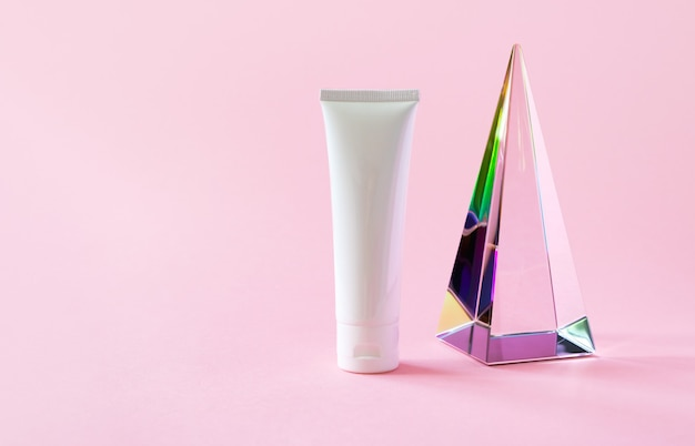 Maquete de tubo de plástico branco com shampoo creme hidratante ou limpador facial e prisma de pirâmide de vidro