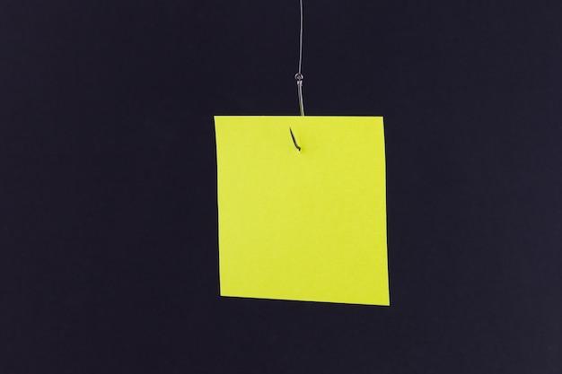 Maquete de um memorando amarelo em branco com espaço para cópia pendurado em um anzol de pesca