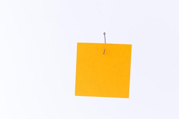 Maquete de um memorando laranja em branco com espaço para cópia pendurado em um anzol de pesca