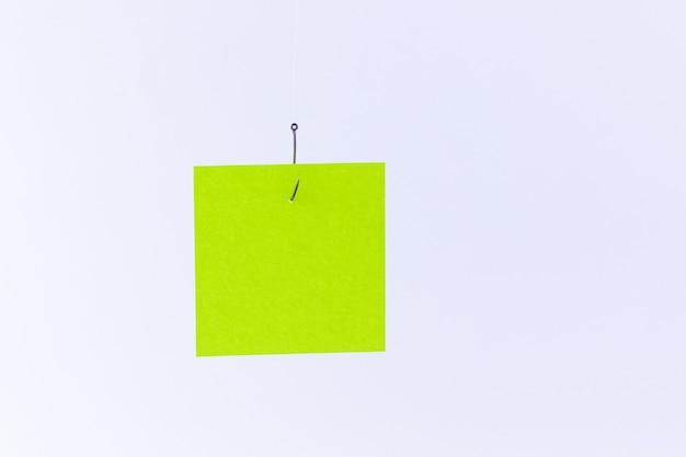 Maquete de um memorando verde em branco com espaço para cópia pendurado em um anzol de pesca