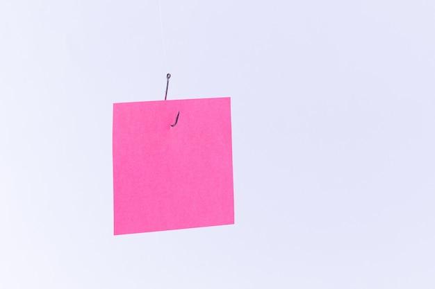 Maquete de um papel de memorando rosa em branco com espaço para cópia pendurado em um anzol de pesca