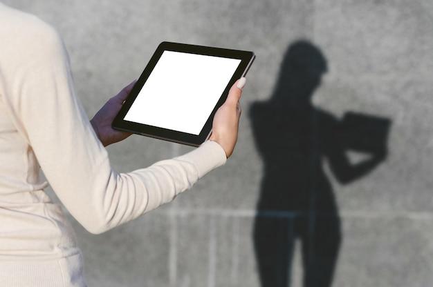 Maquete de um tablet nas mãos de uma menina. contra o fundo de uma parede de concreto cinza, uma silhueta permanece com uma sombra clara.