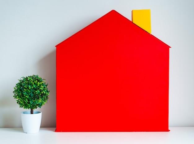 Maquete de uma árvore doméstica de casa vermelha de brinquedo em uma propriedade de parede branca e ideias de conceitos de propriedade ou investimento