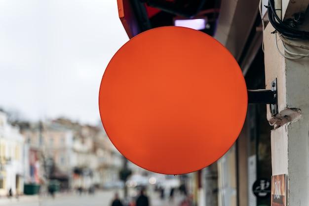 Maquete de uma placa de rua redonda para publicidade ao ar livre no fundo da casa. quadro de publicidade vermelho no prédio