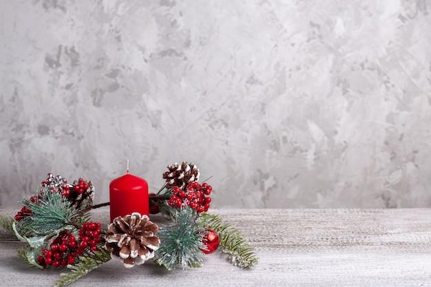 Maquete de vela vermelha de natal e uma coroa de galhos de árvores de natal, cones e frutas vermelhas