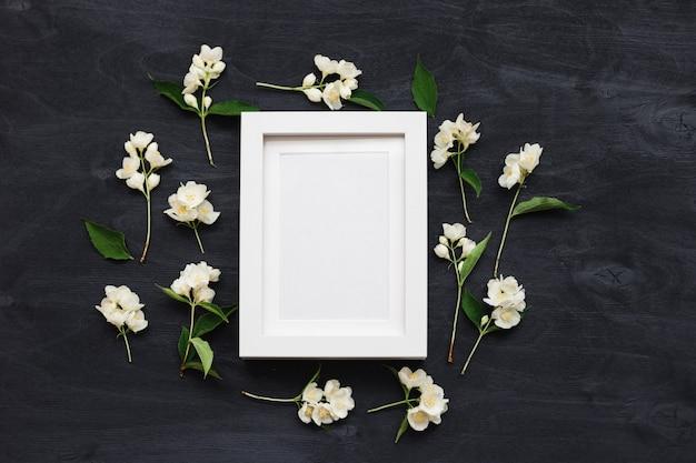 Maquete de vista superior plana leiga de uma moldura em um fundo preto com flores silvestres. foto de layout na moda bonita.