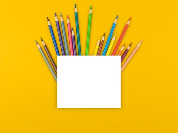 Maquete de volta às aulas, composição criativa plana com lápis de cor e papel branco em branco na mesa amarela, vista de cima e foto do espaço de cópia