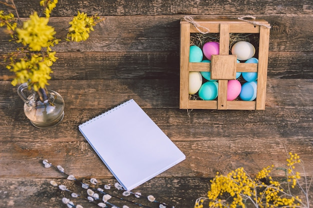 Maquete do bloco de notas com flores e ovos de páscoa. no contexto de uma velha placa.