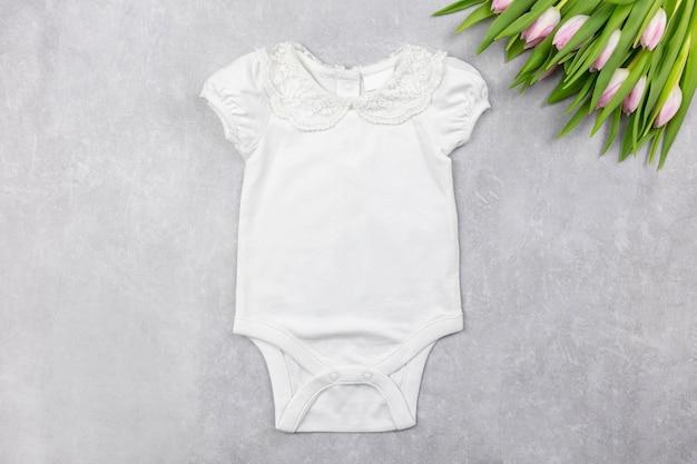 Maquete do body da menina branca com flores de tulipas cor de rosa na superfície de concreto cinza