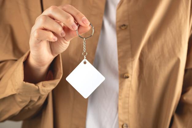Maquete do chaveiro para exibir o modelo do chaveiro do projeto na mão da mulher em branco losango sublimação branca ke ...