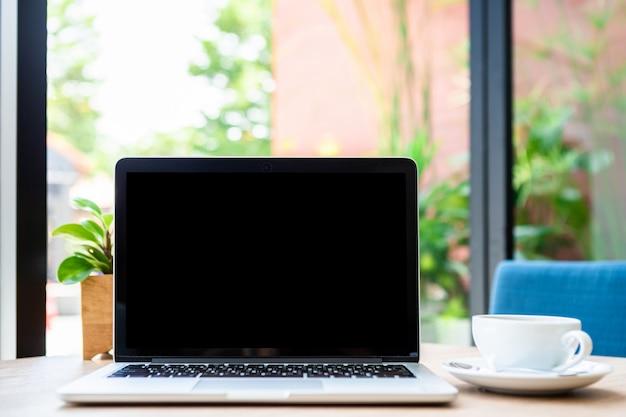 Maquete do computador portátil com tela vazia com uma xícara de café na mesa da cafeteria, tela preta