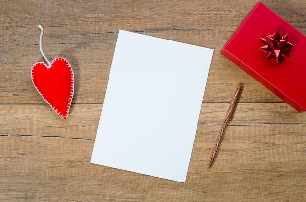 Maquete do dia dos namorados. papel em branco sobre fundo de madeira
