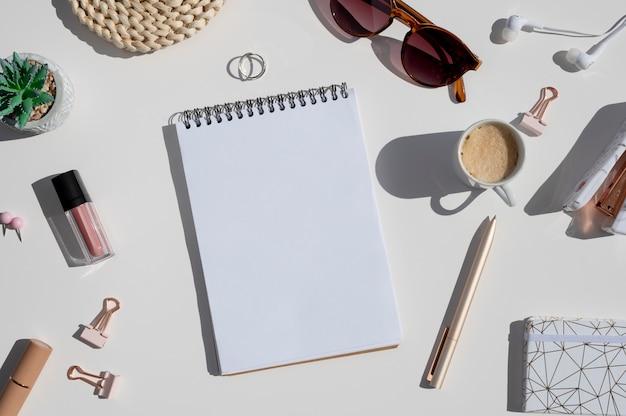 Maquete do espaço de trabalho criativo feminino. vista superior da mesa branca na luz do sol com acessórios femininos, caderno espiral aberto e xícara de café.