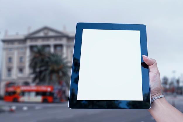 Maquete do tablet na mão da menina, com uma tela branca no fundo de um ônibus turístico e palmeiras. turismo e viagens online.