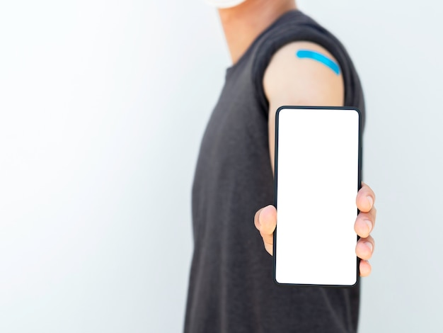 Maquete do telefone, tela branca em branco no smartphone mostrando pelo homem vacinado que usava uma máscara facial médica e curativo azul no ombro, isolado no bakground branco com espaço de cópia.