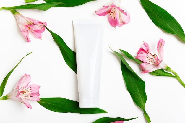 Maquete do tubo em branco de creme para as mãos em fundo branco floral.
