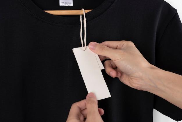 Maquete em branco preto t-shirt e etiqueta em branco tag para publicidade.