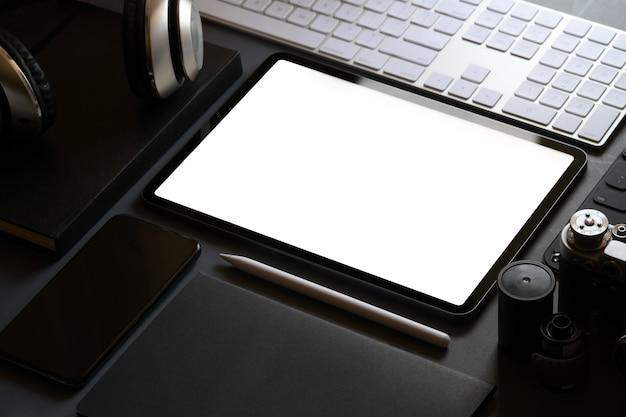 Maquete escritório estacionário com tablet de tela em branco na mesa de trabalho de couro escuro
