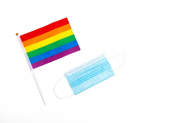 Maquete feita com a bandeira do orgulho lgbt com o coração e a máscara médica