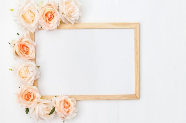 Maquete feita com flores cor de rosa em fundo branco de madeira