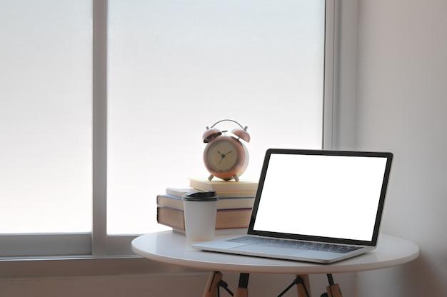 Maquete laptop e copo de café de papel com livros e despertador na mesa no escritório em casa.