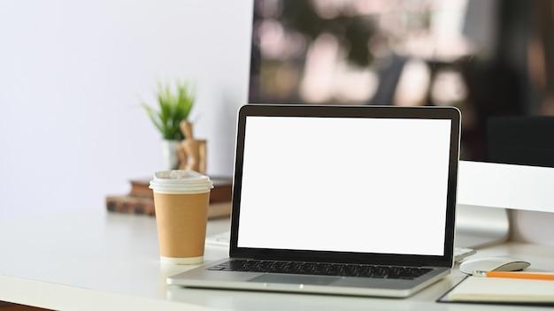 Maquete laptop e copo de papel de café no espaço de trabalho com profundidade de arquivado.