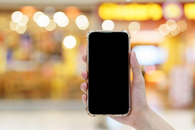 Maquete, mãos segurando um celular de tela preta em branco em uma loja de departamentos desfocada, conceito de pagamento digital