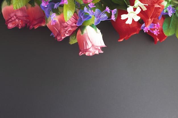 Maquete memorial com flores artificiais sobre um fundo escuro