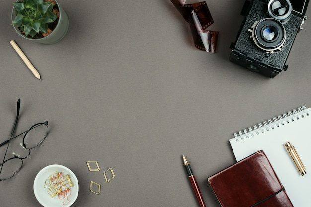 Maquete minimalista elegante com notebook, planejador, óculos, caneta e vintage câmera em fundo cinza na copyspace
