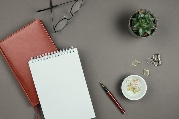 Maquete minimalista elegante com notebook, planejador, óculos e caneta em fundo cinza na copyspace
