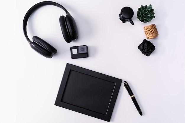 Maquete, moldura, câmera de ação, fones de ouvido, caneta e cacto.