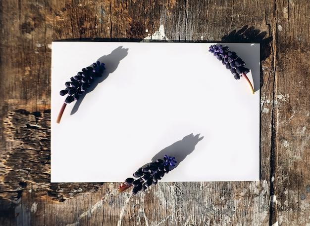 Maquete natural com cartão de papel em branco para texto com flores de jacinto na mesa de madeira