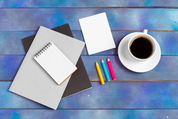 Maquete para lista de verificação, papel vazio nota com uma xícara de café em madeira azul. escritório, escritor ou conceito de estudo