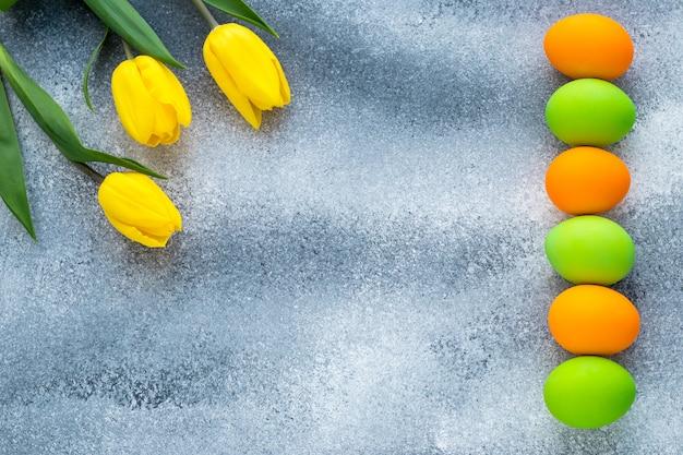 Maquete pascal com espaço de texto. quadro festivo da páscoa com ovos coloridos e tulipas amarelas sobre fundo cinza de concreto.