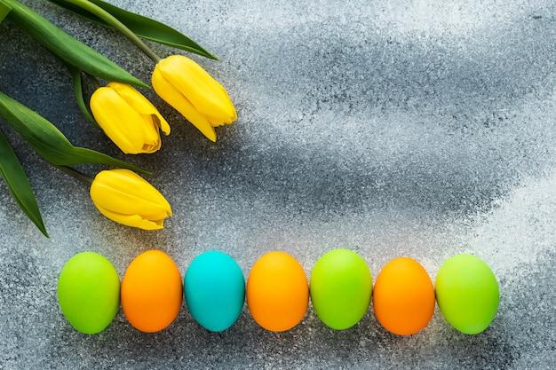 Maquete pascal, cópia espaço. ovos de páscoa e flores da primavera na parede de concreto cinza. decoração do feriado