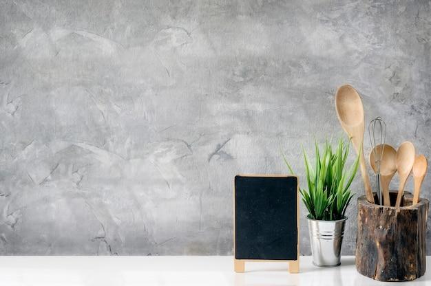 Maquete pequena placa preta e colher de pau na velha caixa de madeira na mesa branca