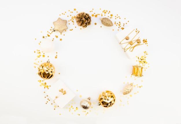Maquete plana de natal com moldura redonda feita de bolas de natal douradas e decorações