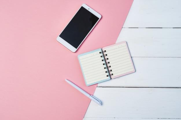 Maquete plana leiga composição com smartphone e o bloco de notas em um fundo azul e rosa. área de trabalho com espaço de cópia