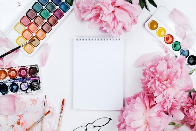 Maquete plana linda feminina com notebook, material de papelaria, aquarelas e peônias rosa em branco