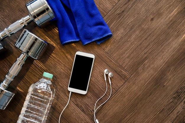 Maquete smartphone com halteres de metal, garrafa e fone de ouvido