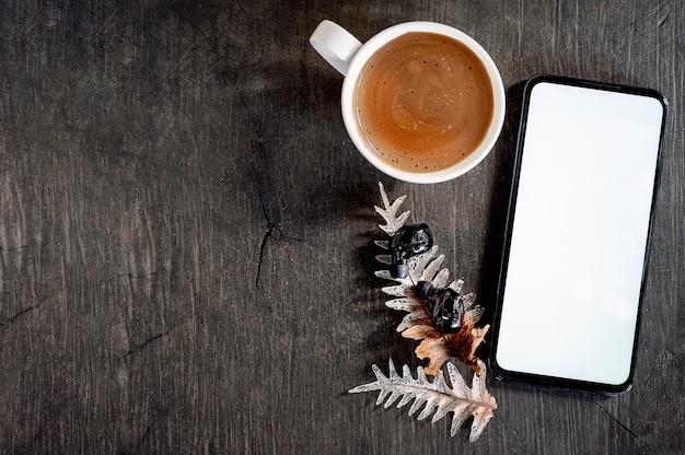 Maquete smartphone com tela em branco e fone de ouvido no fundo de madeira.