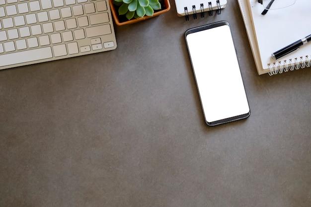 Maquete smartphone com tela vazia no espaço de trabalho.