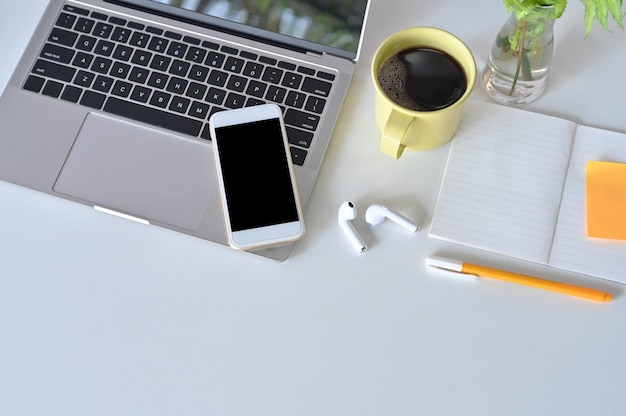 Maquete smartphone, laptop, fone de ouvido na mesa de escritório com uma xícara de café.