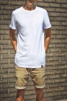 Maquete urbana de roupas. cara jovem ficar em um fundo de parede de tijolos em uma camiseta branca e shorts marrons, sua mão segura nos bolsos de trás. o modelo pode usar para o seu design