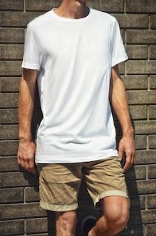 Maquete urbana de roupas. jovem encostado na parede de tijolos em uma camiseta branca e short marrom. modelo pronto para vitrine.